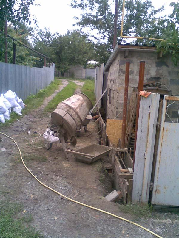 Установка бетономешалки возле опалубки фундамента забора повышает производительность строительных работ