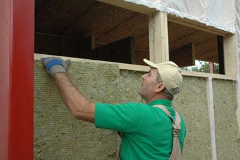 Отличительной чертой каркасно-панельного дома являются специальные теплоизолирующие панели, которые легко монтировать.